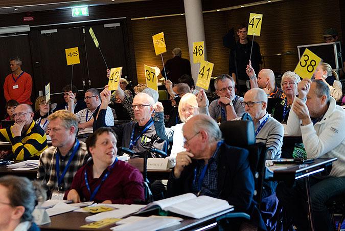Personer sitter med gula lappar på pinnar som de lyfter i luften när de röstar.