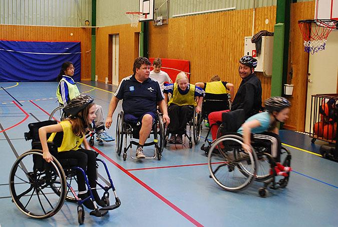 Barn kör rullstol i en idrottshall. Några har gula västar. Två vuxna är också med.