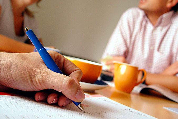 En person skriver på ett papper. I bakgrunden samtalar två andra personer. På bordet står kaffekoppar.
