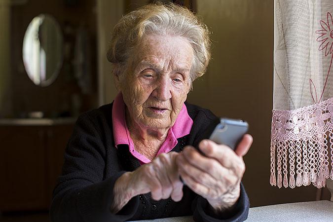 En äldre kvinna sitter vid ett bord och trycker på en smart mobil