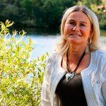 Porträtt av Mie Karlsson. Hon står vi en buske med ett vattendrag i bakgrunden.