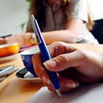 Möte pågår vid bord med pennor och kaffekoppar