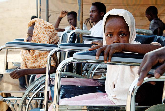 En flicka sitter i en alldeles för stor rullstol och tittar in i kameran. I Bakgrunden syns fler rullstolar och några män som verkar vänta på något.