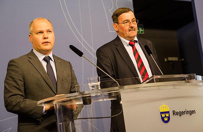 """Morgans Johansson står till vänster bakom ett genomskinligt bord som det står """"regeringen"""" på. Bredvid honom till höger står Lars-Erik Lövdén"""