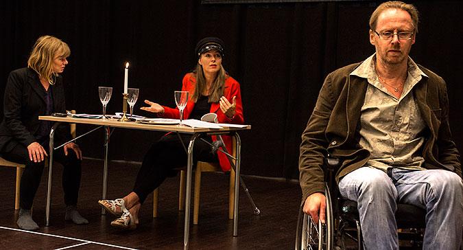 Foto från föreställningen. Hans Sjöberg sitter i förgrunden till höger och två andra personer sitter vid ett bord i bakgrunden. En har konduktörsmössa