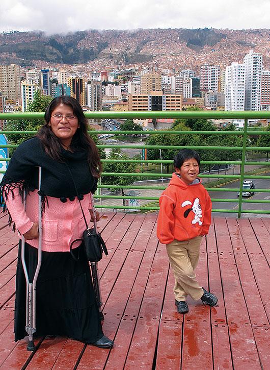 Gladys Quispe och hennes son står på en bro. I bakgrunden ser man La Paz där husen trängs på bergssidan och molnen hänger lågt..