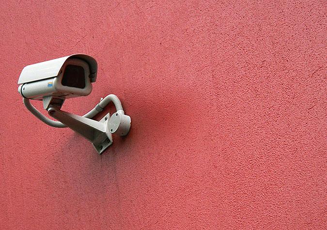 En övervakningskamera på en röd vägg