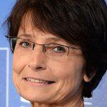 Porträtt av Marianne Thyssen mot en blå bakgrund där EUs flagga syns.
