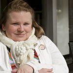 Maia Joahnsson sitter vid bord i vit kofta och halsduk.
