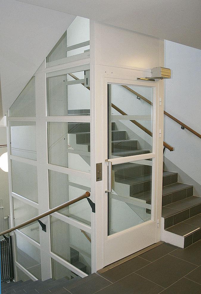 Ett trähus i vitt med mörkt klinker golv. I mitten av trapphuset finns en hiss trumma av glas och stål.