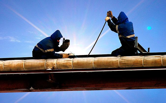 Två personer jobbar med ett svetsarbete på vad som ser tus om en balk.