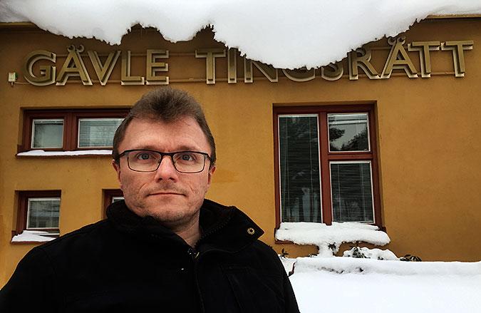 Lars-Göran Waden fram för ett gult hus där det står Gävle tingsrätt. Stora snömassor hänger ner från takfoten.