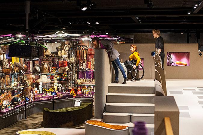 Bild från interiören på utställningen på Världskulturmuseet. Tre personer, varav en i rullstol, står på en plattform och skådar ut över ett rum med färgglada installationer.