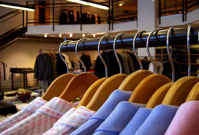 Kläder hänger på galgar i vad som ser ut som en lite mer exklusiv butik