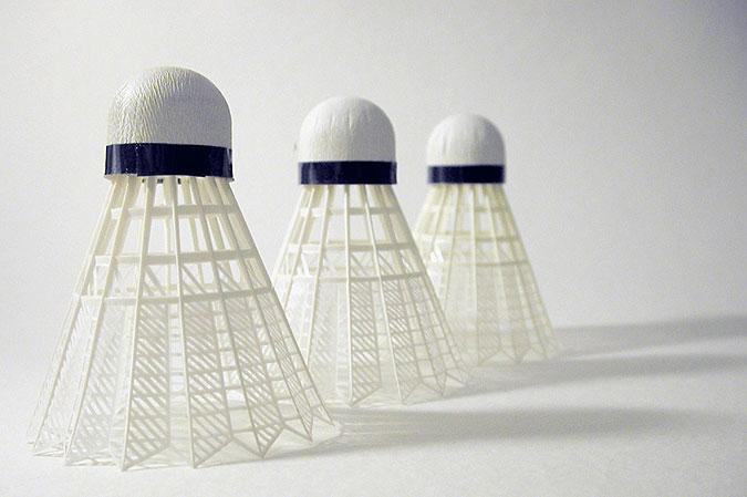 Tre badmintonbollar som står uppställda i rad.