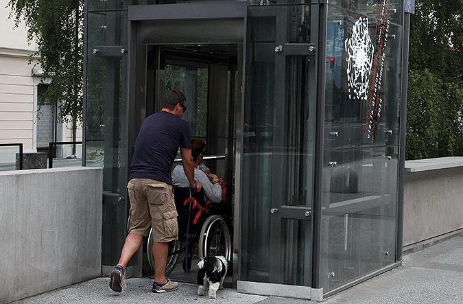 en person hjälper en person i rullstol att koma in i en inglasad hiss. En liten svartvit hund springer bredvid.