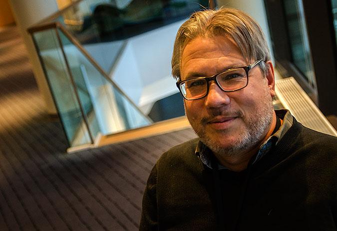 Peter andeberg i en inomhusmiljö med en heltäckningsmatta och en trappa i bakgrunden.