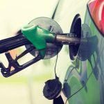 Ett tankhantag på en bensinstation sitter instucket i en grön bil.