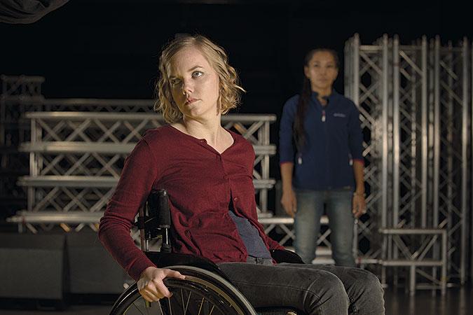 Ylva Andersson sitter i en rullstol i förgrunden. I bakgrunden står hennes assistent.