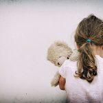 Barn sitter med ryggen mot kameran och kramar en nalle.