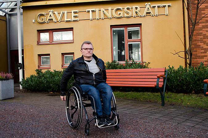 Lars-GÖran Wadén sitter i rullstol fram för ett gult hus som det står Gävle tingsrätt på