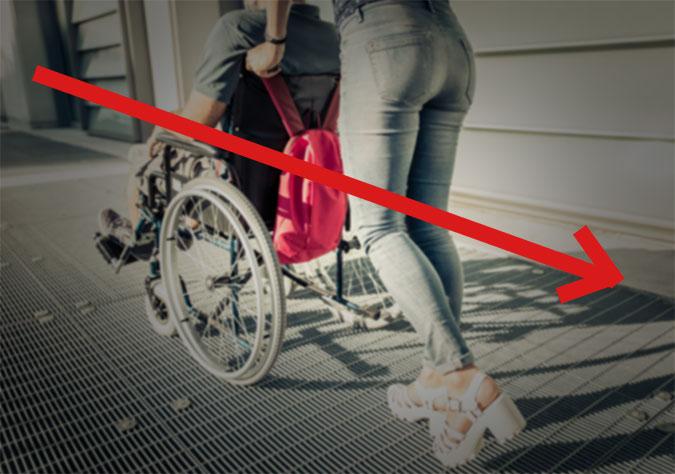 En suddig bild på en person som puttar en annan i rullstol med en röd pil ovanpå bilden som pekar svagt nedåt höger.
