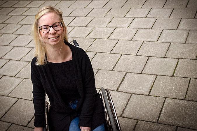 Andrea Bondesson sitter i en rullstol. I bakgrunden syns ett golv av cementplattor.