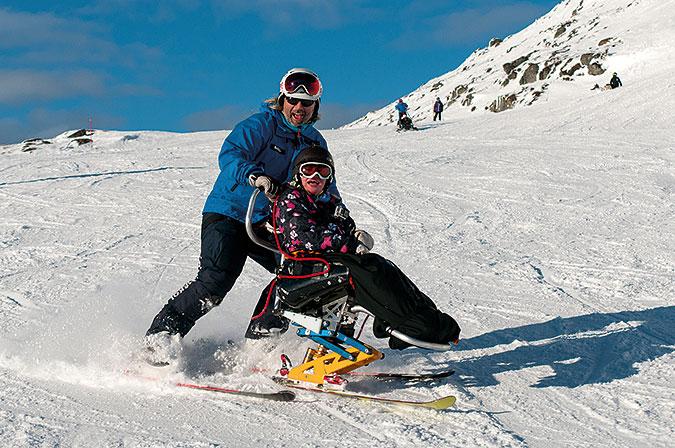 En skidlärare hjälper en sitski-åkare att ta sig ner för en skidbacke.