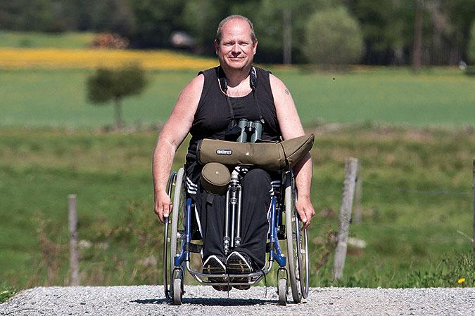 Pelle Aspegren sitter i en rullstol på en grusväg i ett öppet ängs- och åkerlandskap. I knät har han en fågelkikare med fodral och stativ.