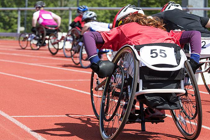 Atleter i rullstol tävlar i ett lopp på en löparbana.
