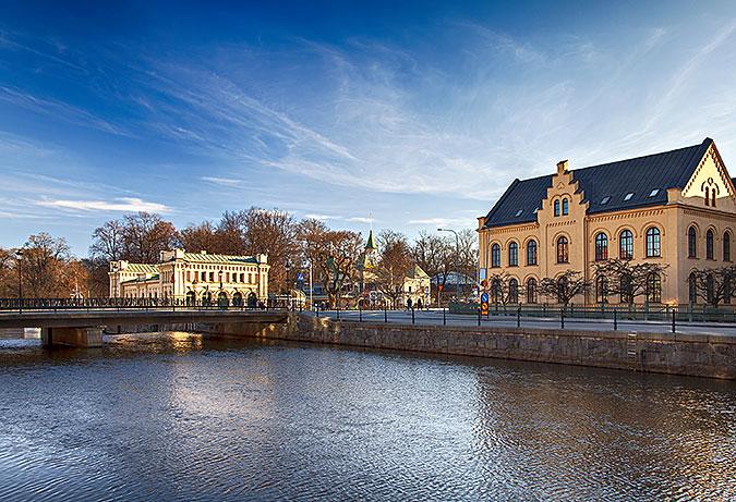 En bild från Uppsala. Två äldre hus i gult med Fyrisåns vattenspegel framför. (Foto