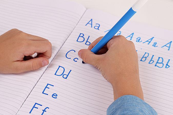 Barn tränar på att skriva bokstäver i ett linjerat block.