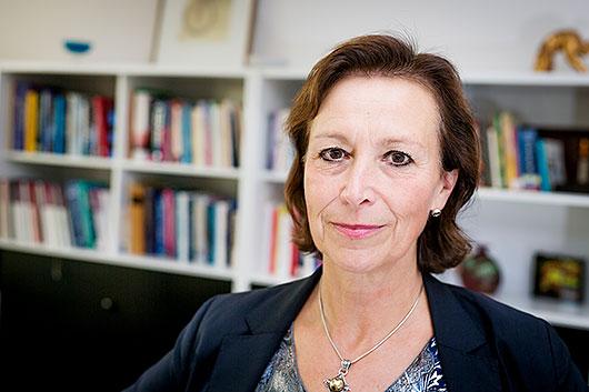 Porträtt av Kerstin Tham framför en bokhylla.