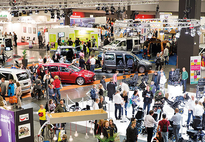 En stor hall med utställningsmontrar, med bland annat bilar, och en massa människor.