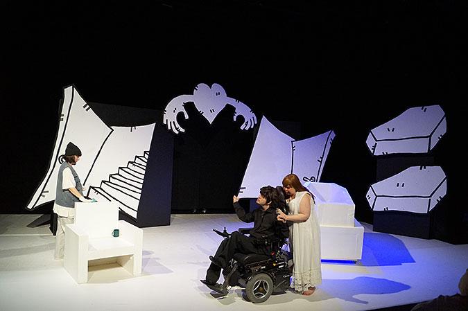 Scenbild från föreställningen. En svartklädd person i elrullstol och en person i vit klänning.