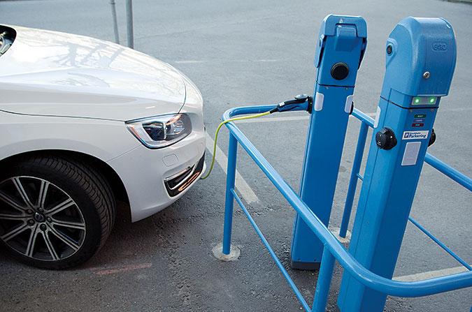 En vit bil laddar vid en blå laddstolpe. En sladd går från stolpen till bilen. Runt stolpen står ett blått staket.