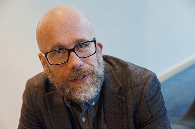 Porträtt av en man med skägg och glasögon mot en ljusblå bakgrund