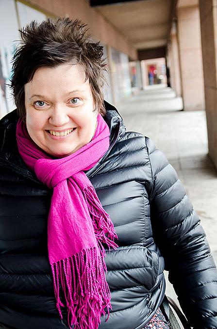 Sari Nykvist iklädd svart jacka och rosa halsduk. Utomhus i en arkad.