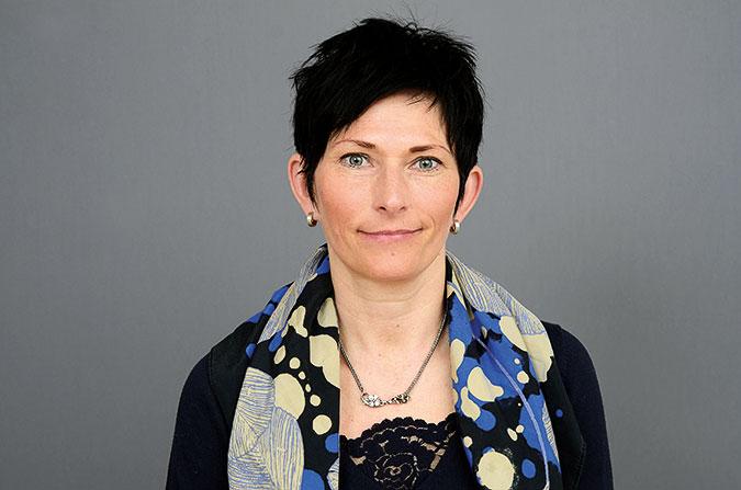 Porträttfoto av en kvinna mot grå bakgrund.
