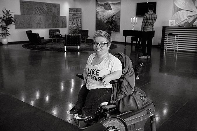 Ulrika Eriksson sitter i en elrullstol i ett stort rum med tavlor på väggarna.