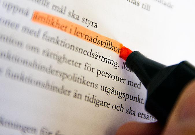 En hand markerar med en rosa märkpenna texten jämlikhet i levnadsvillkor i en längre text på ett papper.