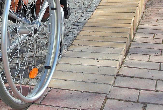 en rullstol balanserar när kanten på en ramp som inte har något skydd för avåkning.