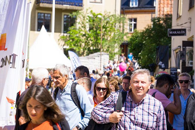 Många människor rör sig i solskenet på en gata i Visby som är kantad av rollups och tält från olika aktörer.