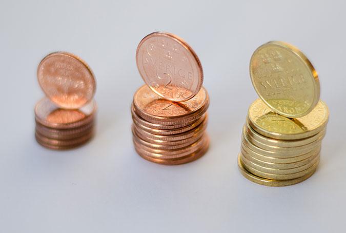 Tre staplar med mynt i olika valörer.