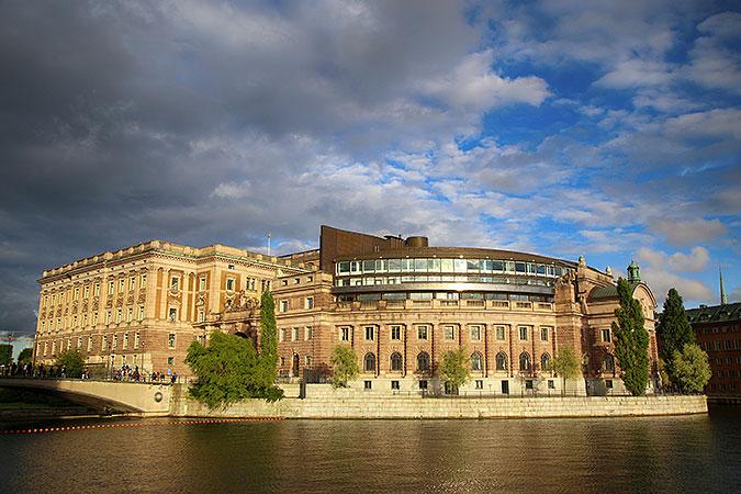 Riksdagshuset sett från nordväst under en blå himmel beströdd med gråa, lite smått hotfulla moln.