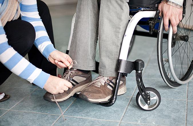 Armarna syns av en person som knyter skorna på en person som sitte i rullstol.
