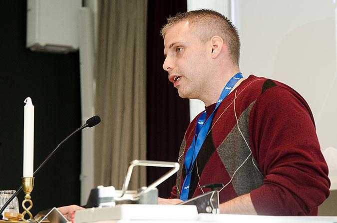 En man i röd tröja pratar i en mikrofon. han sitter bakom ett bord som det står ett ljus på.