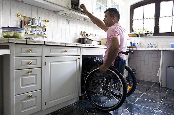 En man som använder rullstol jobbar i köket.