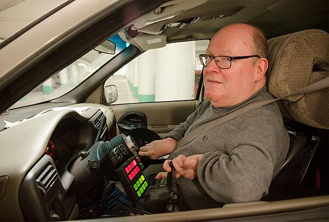 En man på förarplatsen i en bil. Här finns ingen vanlig ratt.Istället styr han med en spak och kontrollerar andra funktioner med särskilda knappar som syns i bilden.