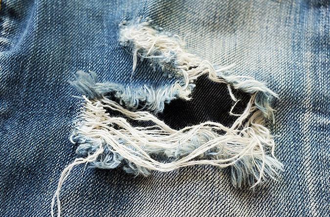 Ett hål i ett par slitna blå jeans.